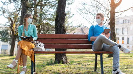 A young woman and a young man sitting wearing masks, sitting on opposite ends of a park bench